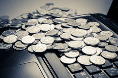 Coins on laptop Stock Image