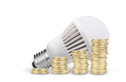 Coins and LED bulb. Money saved with LED bulb on white background Stock Image