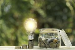Coins and light bulb put on the table for saving money,energy concept on nature background.  royalty free stock images