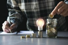 Coins and light bulb put on the wooden for saving money,energy c. Oncept in dark background stock images