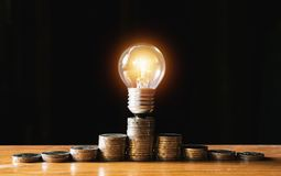 Coins and light bulb put on the wooden for saving money,energy c. Oncept in dark background royalty free stock photos