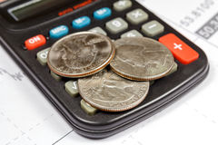 Coins lying on the surface of the electronic calculator. Focus in the foreground Stock Photo