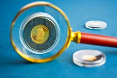Coins and magnifier. Gold coins and magnifier on blue background Stock Photography