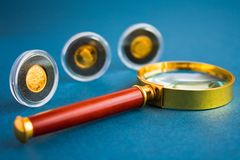 Coins and magnifier. Gold coins and magnifier on blue background Stock Images