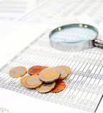 Coins and a magnifier on documents. Royalty Free Stock Photo