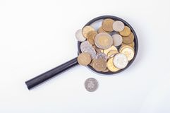 Coins on magnifying glass Stock Photography