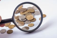 Coins on magnifying glass Royalty Free Stock Photo