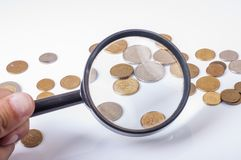 Coins on magnifying glass Stock Images