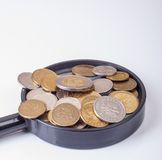 Coins on magnifying glass Royalty Free Stock Images
