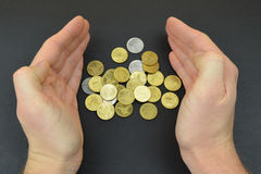 Coins between man hands on black background. Bronze coins Stock Photography