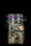 Coins in a Mason Jar. A Vertical view of American coins in a glass mason jar on a black background with space for text at the top Royalty Free Stock Images
