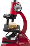 Coins and microscope. Coins in red microscope isolated in white stock images