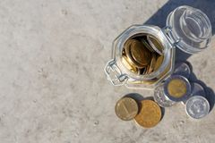 Coins mix fall out of glass jar on floor Royalty Free Stock Photo