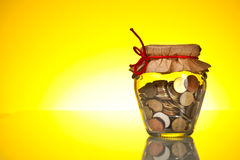 Coins in money jar. On yellow background stock image