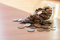 Coins in money jar with sunset light in saving money Stock Photo