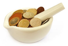 Coins in a mortar with pestle Royalty Free Stock Photography