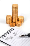 Coins and notepad Royalty Free Stock Photos