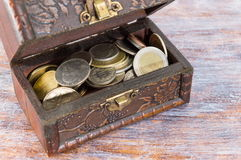 Coins in an old wooden box Stock Photography
