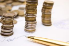 Coins On Written Contract With Pen Royalty Free Stock Photography