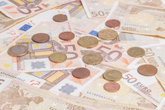 Coins over fifty notes Stock Photography