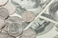 Coins over hundred dollar bills close up view Stock Images