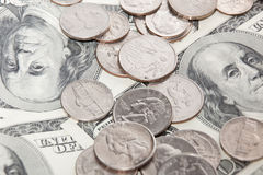 Coins over hundred dollar bills close up view Royalty Free Stock Photography