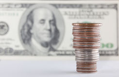 Coins over hundred dollar bills close up view Stock Image