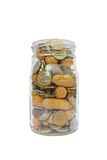 Coins and peanuts in glass jar Stock Image