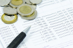 Coins and pen on bank statement. Bank statement with money coins and pen Stock Image