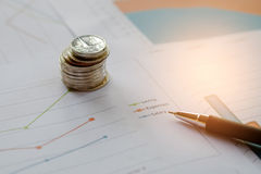 Coins and pen placed on the graph. Concept businness,Coins and pen placed on the graph Royalty Free Stock Photo