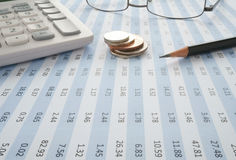 Coins and pencil on top of spreadsheet. With glasses and calculator Stock Photography