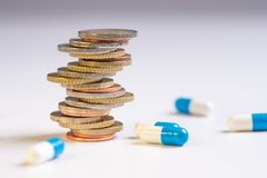 Coins are placed among themselves in different positions next to the blue and white pills. Copy space for text. Rising drug prices stock photography