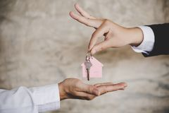 Woman handing over the house keys to a new home inside empty gray colored room stock images