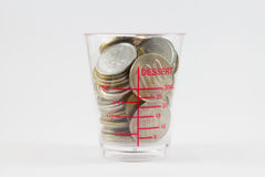 Coins in the plastic cup. And white background royalty free stock photo