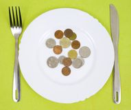 Coins on a plate. Coins on a white plate stock photos