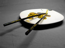 Coins on the plate. Bamboo chopsticks on white and black plate containing stacks of bright copper coins in hard light and shadow against grey background. on Stock Photography