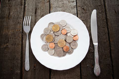 Coins on a plate. With fork and knife on wooden table stock image