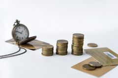 coins, pocket watch on chain, multiple Bank cards on white background, time, money stock image