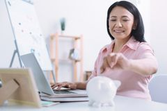 Happy brunette putting money into piggy bank. It is for coins. Positive pregnant woman keeping smile on her face and raising left hand while looking forward Stock Photography