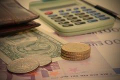 Coins, purse and calculator Stock Photos