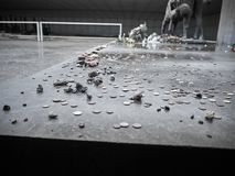 Coins put near a memorial statue in remembrance of the victims royalty free stock image