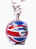 Coins Raining into UK Piggybank. Isolated image of coins falling into a piggy-bank with UK flag printed on it Royalty Free Stock Photos