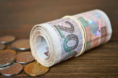 Coins and rolled banknotes Stock Image