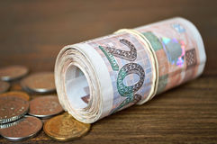 Coins and rolled banknotes Stock Photos