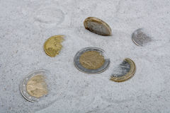 Coins in a sand background Stock Photos