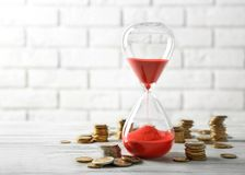 Coins and sandglass. On brick wall background Stock Image
