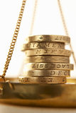 Coins on scale. Pound coins on golden scale Stock Photography