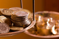 Coins on a scale weight. Vintage scale weights outweigh coins on an old balance Stock Photos