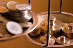 Coins on a scale weight. Vintage scale weights outweigh coins on an old balance Royalty Free Stock Image