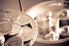 Coins on a scale weight. Vintage scale wheights outweigh coins on an old balance Stock Photo